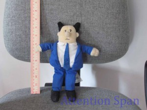Upright ruler next to a standing doll figure of pointy haired boss from Dilbert cartoon
