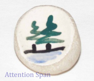 Worry stone with painted scene of trees and water