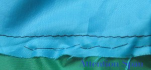 hand and machine stitching on green and blue kite fabric